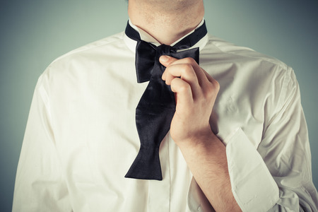 undone: Young man is showing how to tie a formal bow tie