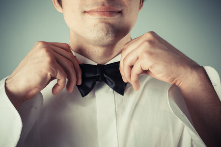 black tie: Closeup on a happy young man tying a bow tie