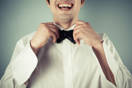 undone: Closeup on a happy and smiling young man tying a bow tie