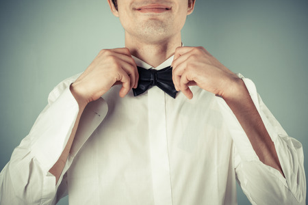 lazo negro: Primer plano de una joven feliz atar una corbata de lazo