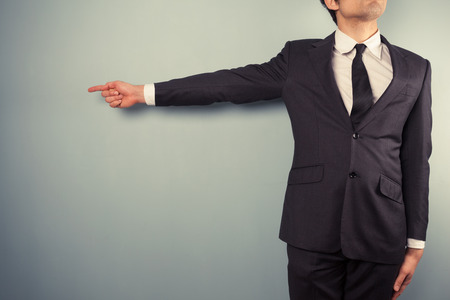 A young businessman is pointing left