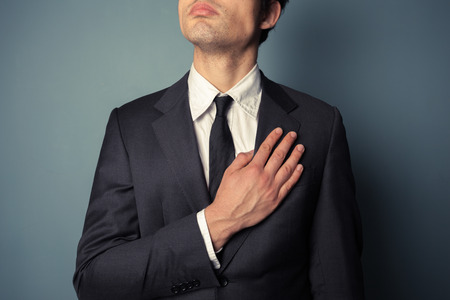 pledge of allegiance: Young businessman is swearing allegiance with his hand on his chest