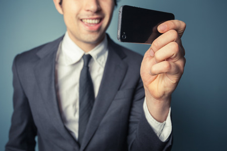 Young businessman is taking a selfie with his smart phone photo