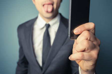 Young businessman is taking a selfie with his smart phone and sticking his tongue out photo