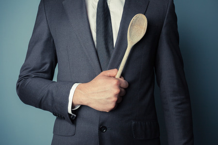 Young businessman is holding a wooden spoon photo