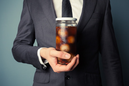 vegtables: Young businessman is holding a jar of pickled onions