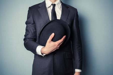 bowler hat: Young man in suit is holding a bowler hat