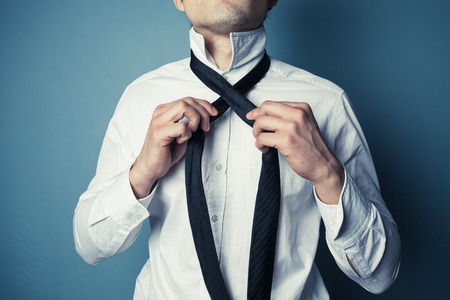 A young man is showing how to tie a necktie photo