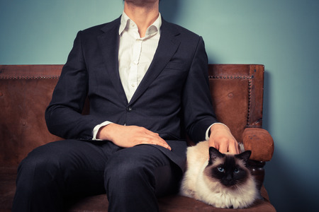 A young man is sitting with his cat on an old sofa photo