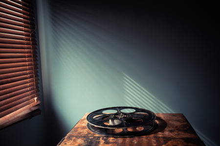 Film reel on a table in a projection room with shadows from the venetian blinds photo