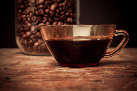 Cup of black coffee and jar of beans on a wooden table photo