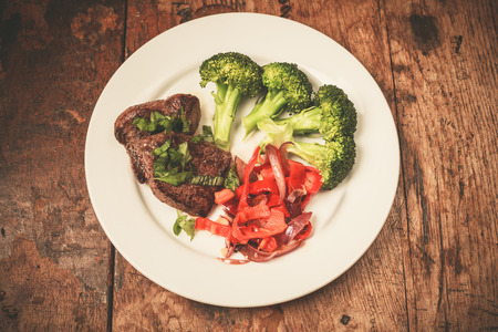 paleolithic: Meat and vegetables including broccoli and red peppers on a plate