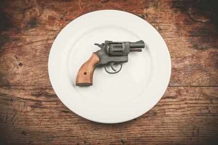 vintage gun: A revolver lying on a white plate