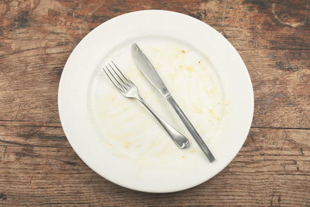 Dirty plate and cutlery on a wood table photo