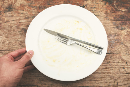 Dirty plate and cutlery with a man's hand next to it Stock Photo