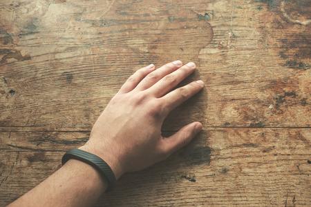 armband: Mano sul tavolo di legno che indossa un bracciale fitness tracking