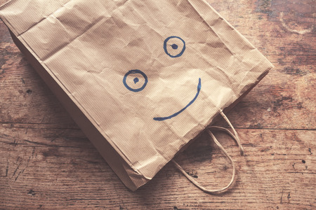 paper bag: A paperbag with a smiling face painted on it lying on a wood table Stock Photo