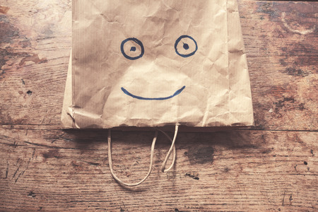 paperbag: A paperbag with a smiling face painted on it lying on a wood table Stock Photo
