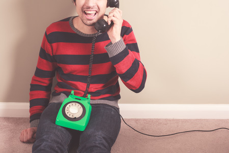 Happy young man is talking on the telephone photo