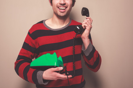 A happy young man is answering the telephone photo