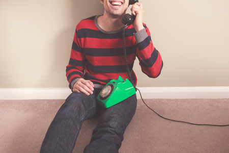 Happy young man is sitting on the floor and talking on the telephone photo