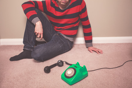 mesmerized: A young man is sitting on the floor and is desperately waiting for a phone call