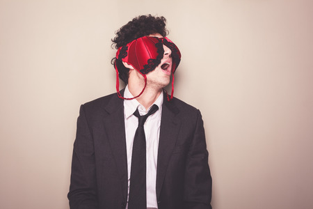 sexy bra: Young businessman is wearing a sexy bra on his face Stock Photo