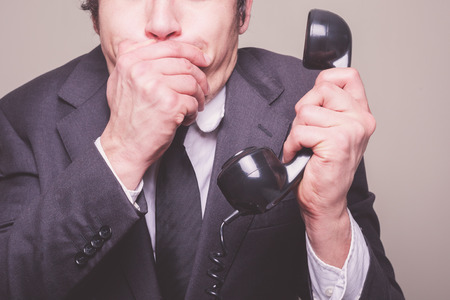 A young businessman is on the phone and covering his mouth in shock photo
