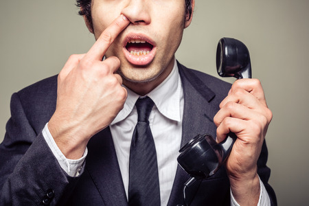 nose picking: Young incompetent businessman is on the phone and is picking his nose