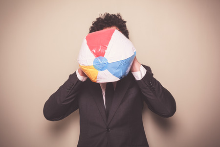 A businessman is blowing up a multi colored beach ball photo