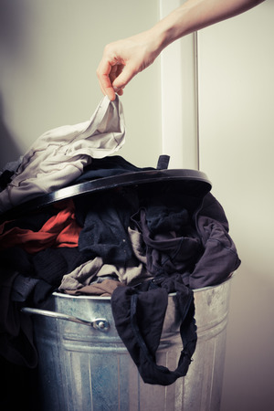 Young woman is sorting out her laundry at home photo