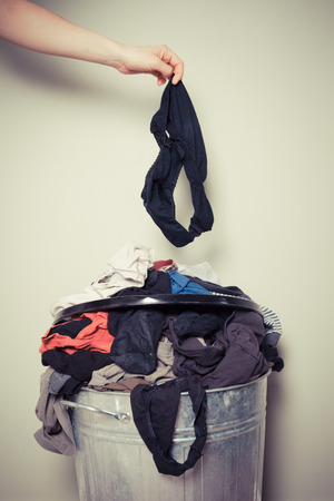 sorting out: Young woman is sorting out her laundry at home