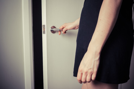Young woman is opening a door into the unknown