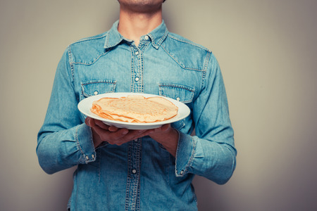 Young man is presenting a plate with a stack of pancakes photo