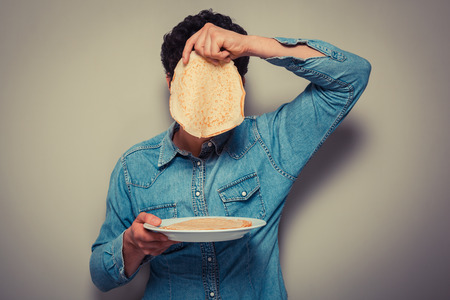 Young man is hiding his face behind a pancake photo