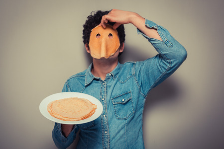 Young man has cut eyeholes in a pancake and is wearing it on his face photo