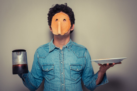Young man has cut eyeholes in a pancake and is wearing it on his face while holding  a pot of coffee photo