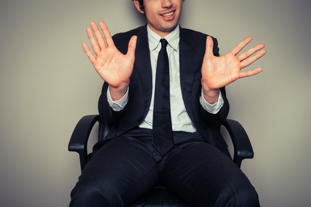 convey: Businessman in office chair showing his palms to convey a clean conscience Stock Photo