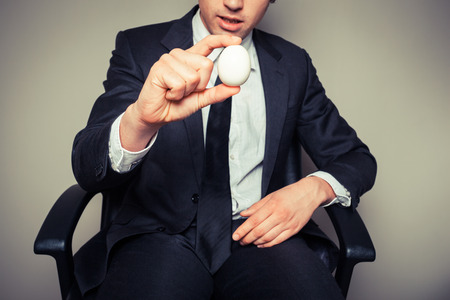 A young businessman sitting in an office chair is holding a boiled egg photo