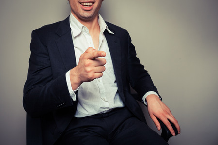 Happy businessman is sitting in an office chair and is laughing and pointing photo