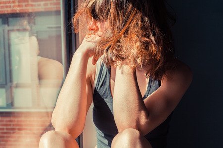 Young woman is sitting in the sunlight on a window sill and looking out