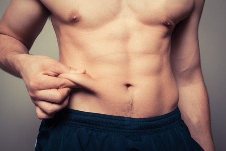 shirtless man: Fit young man pinching the fat on his stomach Stock Photo