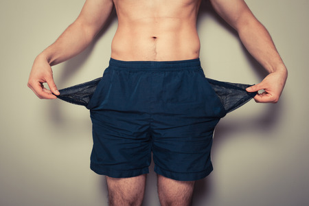Athletic young man is showing his empty pockets photo