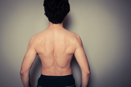 Rear view shot of athletic young man flexing his muscles photo