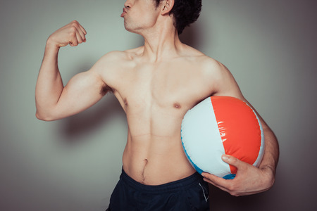 beach hunk: An athletic young man is holding a beach ball Stock Photo