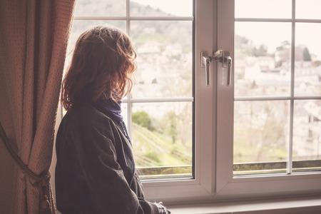ventanas: La mujer joven está mirando por la ventana