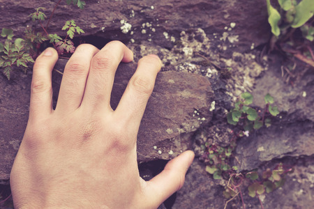 A man's hand is grabbing onto a rock Stock Photo - 27695213
