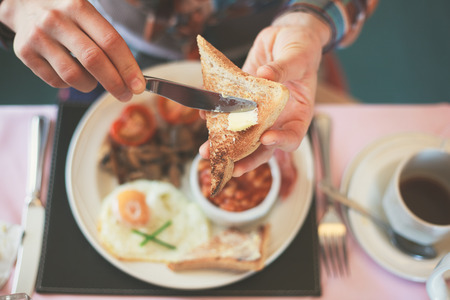 english food: Closeup on a young womans hands as she is having breakfast