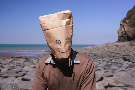 paperbag: Man with a paperbag over his head is sitting on the beach