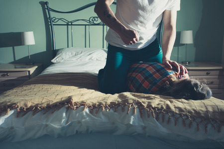 A man is beating his wife on a bed